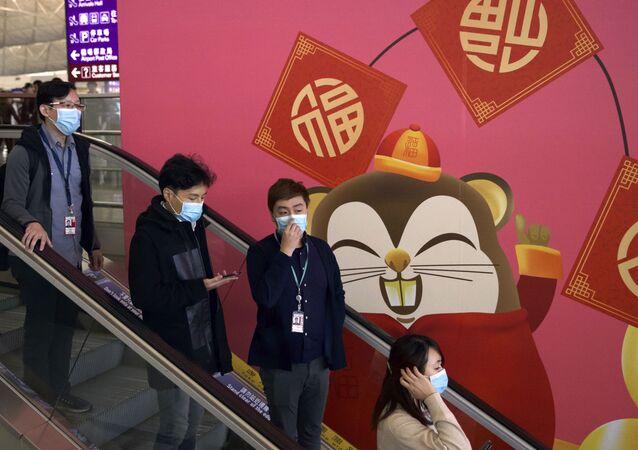 People wear face masks as they ride an escalator at the Hong Kong International Airport in Hong Kong, Tuesday, Jan. 21, 2020