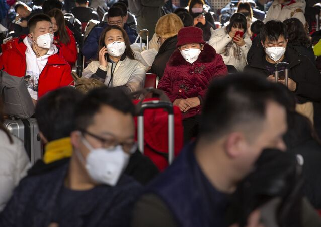 Travelers wear face masks as they sit in a waiting room at the Beijing West Railway Station in Beijing, Tuesday, Jan. 21, 2020