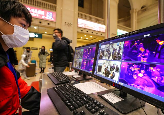 A staff member wearing a mask monitors thermal scanners that detect temperatures of passengers at the security check inside the Hankou Railway Station in Wuhan, Hubei province, China January 21, 2020