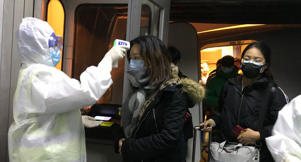Health Officials in hazmat suits check body temperatures of passengers arriving from the city of Wuhan Wednesday, Jan. 22, 2020, at the airport in Beijing, China