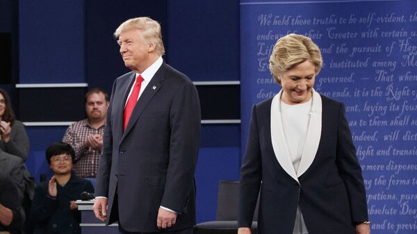 Republican presidential candidate Donald Trump, left, and Democratic presidential candidate Hillary Clinton walk to their seats after arriving for the second presidential debate at Washington University, Sunday, Oct. 9, 2016, in St. Louis - Sputnik International