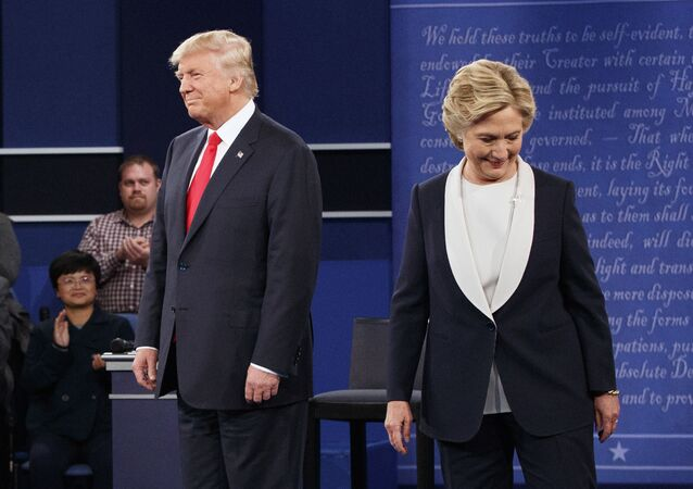 Republican presidential candidate Donald Trump, left, and Democratic presidential candidate Hillary Clinton walk to their seats after arriving for the second presidential debate at Washington University, 9 October 2016, in St. Louis