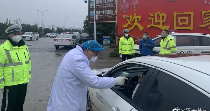 A doctor scans a driver's temperature amid coronavirus outbreak in China