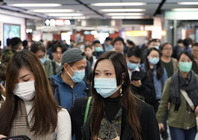 Passengers wear masks to prevent an outbreak of a new coronavirus in a subway station, in Hong Kong, Wednesday, Jan. 22, 2020