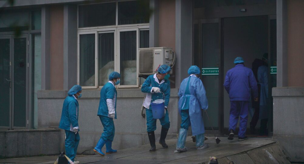 Hospital staff wash the emergency entrance of Wuhan Medical Treatment Center, where some infected with a new virus are being treated, in Wuhan, China, Wednesday, Jan. 22, 2020.