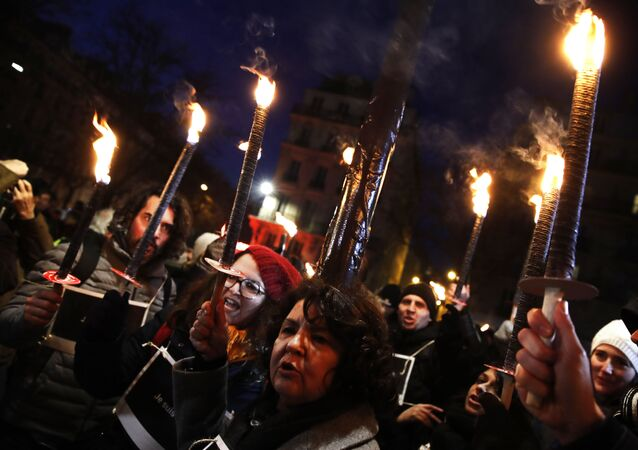 Demonstrators take part in a march with torches during a protest against pension reforms in Paris, France, Thursday, Jan. 23, 2020