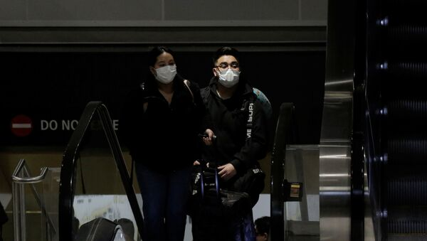 Travellers wearing masks arrive on a direct flight from China, after a spokesman from the U.S. Centers for Disease Control and Prevention (CDC) said a traveller from China had been the first person in the United States to be diagnosed with the Wuhan coronavirus, at Seattle-Tacoma International Airport in SeaTac, Washington, U.S. January 23, 2020 - Sputnik International