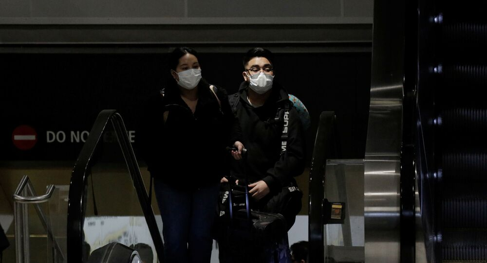 Travellers wearing masks arrive on a direct flight from China, after a spokesman from the U.S. Centers for Disease Control and Prevention (CDC) said a traveller from China had been the first person in the United States to be diagnosed with the Wuhan coronavirus, at Seattle-Tacoma International Airport in SeaTac, Washington, U.S. January 23, 2020