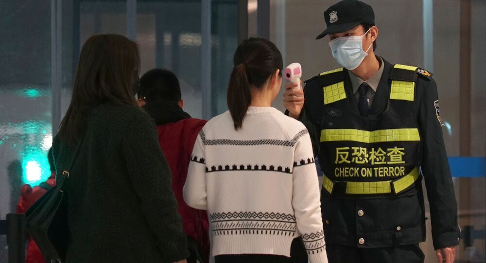 An airport staff member uses a temperature gun to check people leaving Wuhan Tianhe International Airport in Wuhan, China