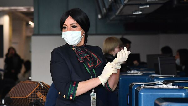 An Airport Employee Puts on Protective Gloves and Respiratory Mask at Rome's Fiumicino Airport - Sputnik International