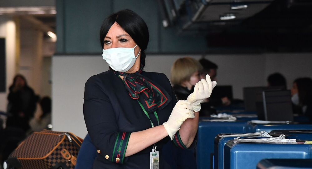 An Airport Employee Puts on Protective Gloves and Respiratory Mask at Rome's Fiumicino Airport