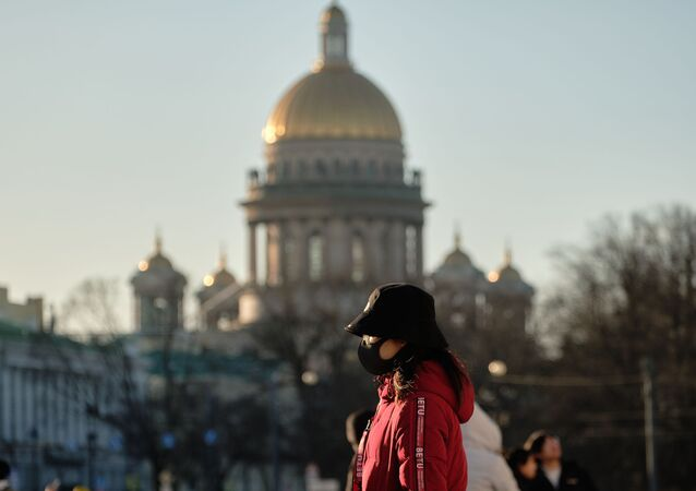 Chinese tourist in a protective mask on Palace Square in St. Petersburg