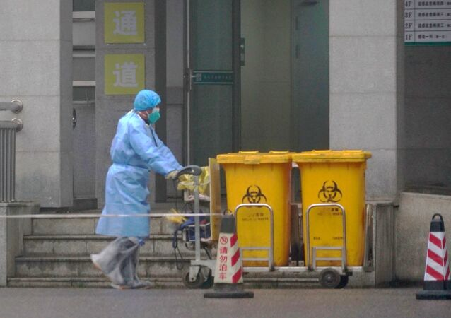FILE - In this Wednesday, Jan. 22, 2020, file photo, a staff member moves bio-waste containers past the entrance of the Wuhan Medical Treatment Center in Wuhan, China, where some people infected with a new virus are being treated.