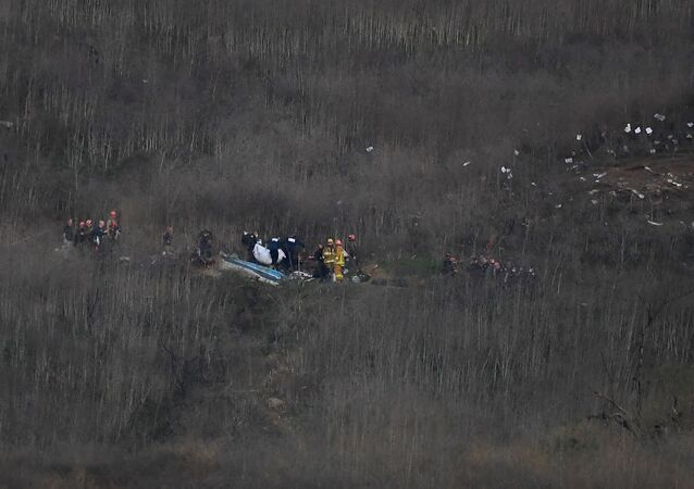 Jan 26, 2020; Calabasas, California, USA;  Members of LA County Fire and LA County corners begin the task of removing bodies from the hillside where the helicopter carrying Kobe Bryant and 8 others crashed in Calabasas, CA