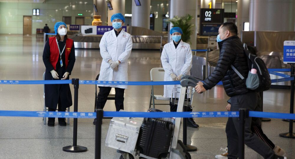 Medical officials monitor a thermal scanner as passengers arrive at the airport in Changsha, Hunan Province