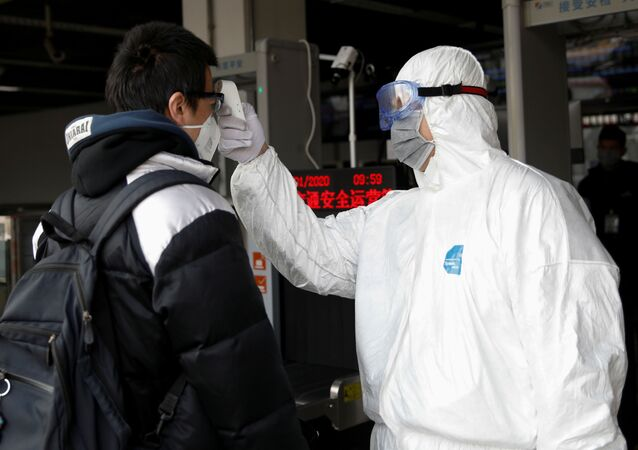 A worker in protective suit uses a thermometer to check the temperature of a man