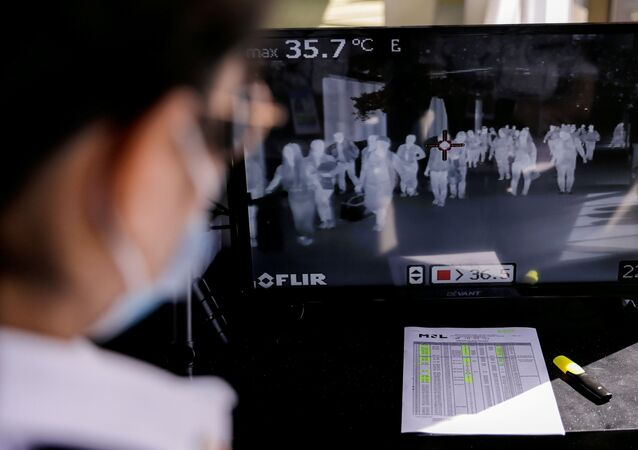 Airport personnel monitor a thermal scanner as passengers arrive at the Ninoy Aquino International Airport in Pasay