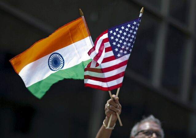 A man holds the flags of India and the U.S. while people take part in the 35th India Day Parade in New York August 16, 2015.