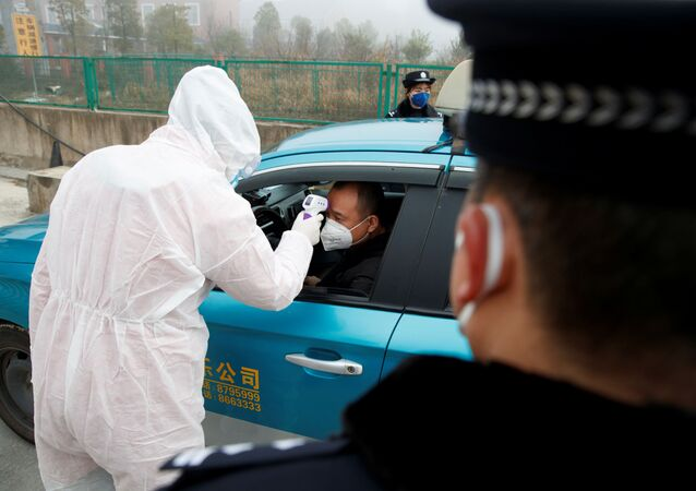 A medical worker in protective suit checks the body temperature of a driver at a checkpoint outside the city of Yueyang, Hunan Province, near the border to Hubei Province that is on lockdown after an outbreak of a new coronavirus, China, January 28, 2020.