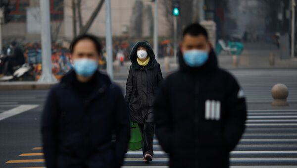 People wearing masks walk across a street as the country is hit by an outbreak of the new coronavirus, in Beijing, China January 28, 2020.  - Sputnik International