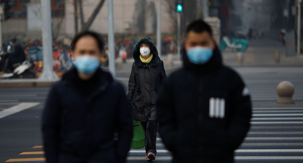 People wearing masks walk across a street as the country is hit by an outbreak of the new coronavirus, in Beijing, China January 28, 2020.