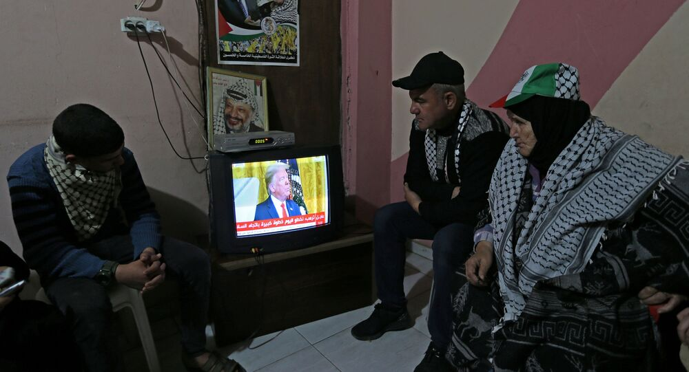 Palestinians watch a television broadcasting the announcement of Mideast peace plan by U.S. President Donald Trump, in the southern Gaza Strip January 28, 2020. REUTERS/Ibraheem Abu Mustafa