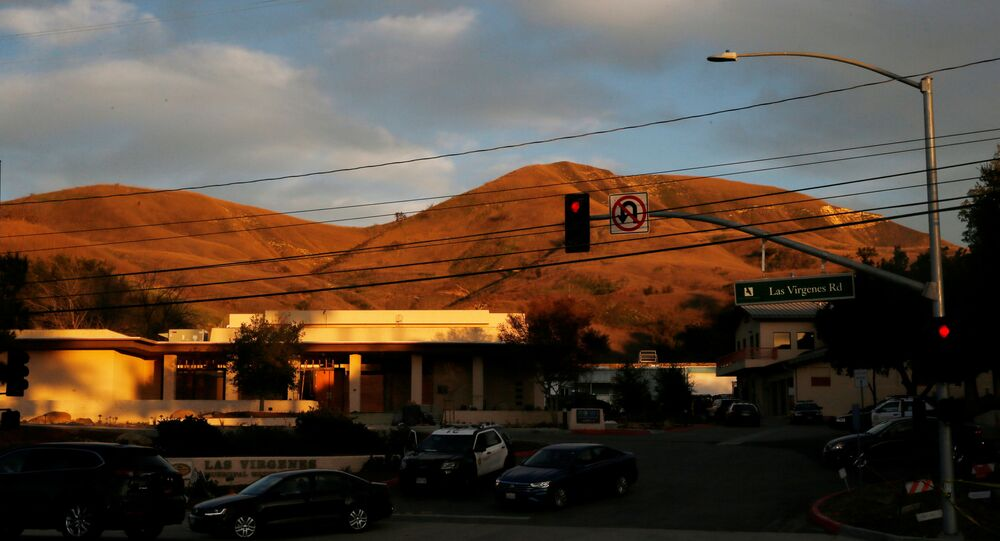 The sun sets on the helicopter crash site of NBA star Kobe Bryant as cars leave the Las Virgenes Municipal Water District parking lot below it in Calabasas, California, U.S., January 27, 2020.