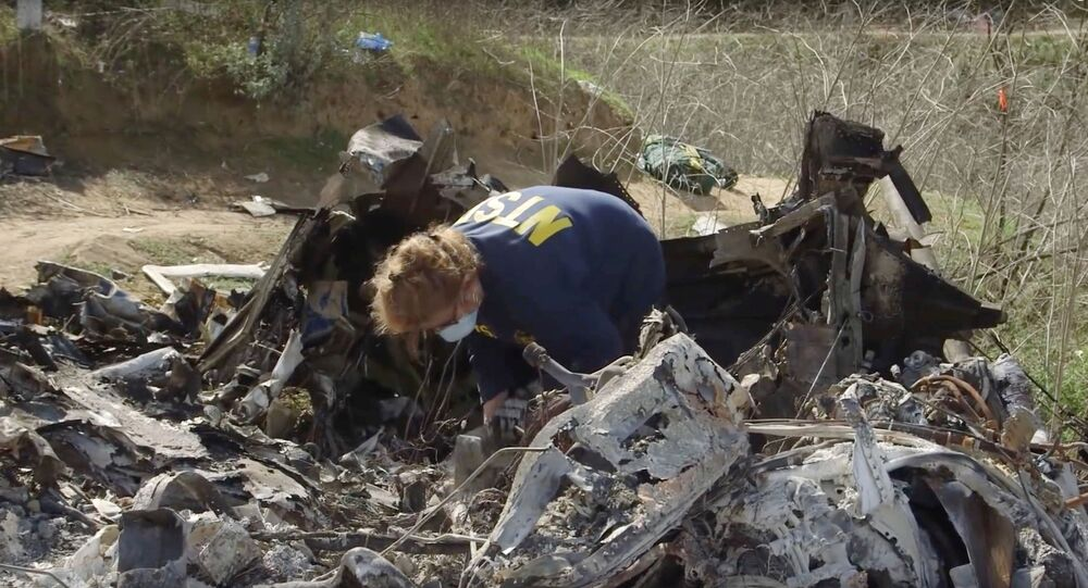 An investigator works at the site of the helicopter crash that killed Kobe Bryant and eight others in a screen grab taken in Calabasas, California, U.S. January 27, 2020 and released by the National Transportation Safety Board.