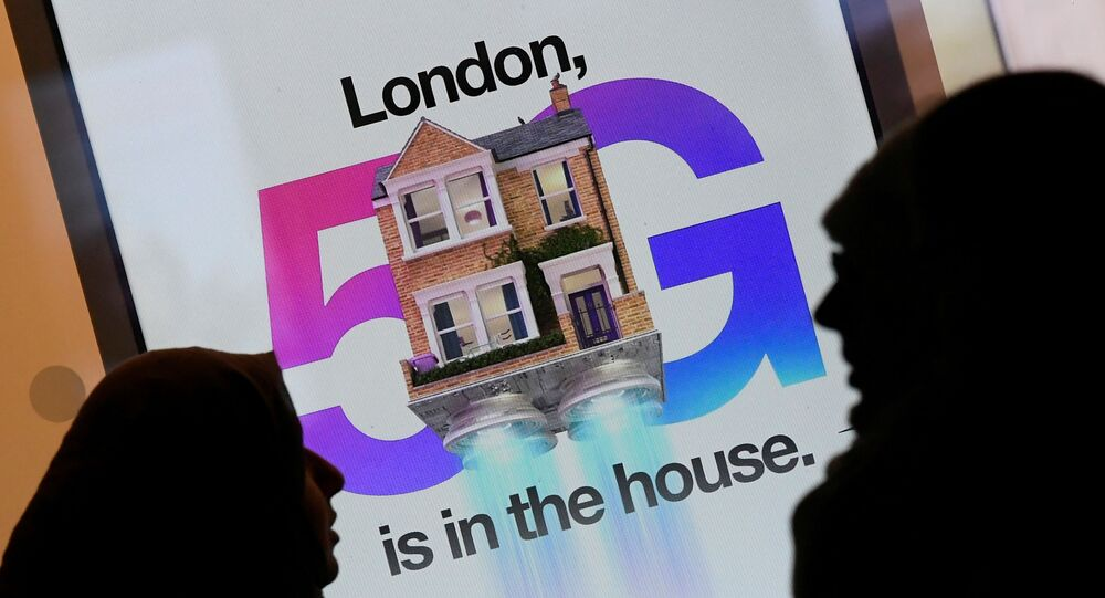 Pedestrians walk past an advertisement promoting the 5G data network at a mobile phone store in London, Britain, January 28, 2020.