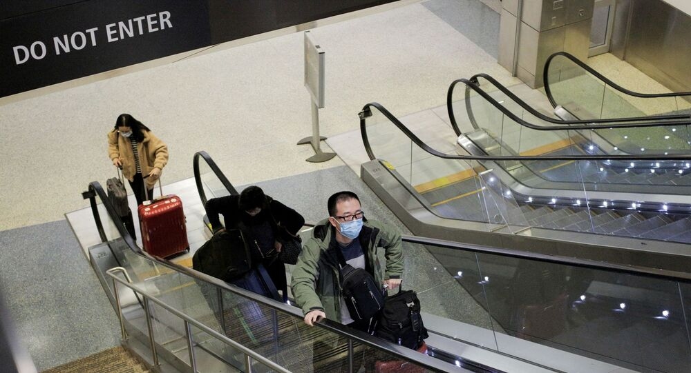 A traveller wearing a mask arrives on a direct flight from China