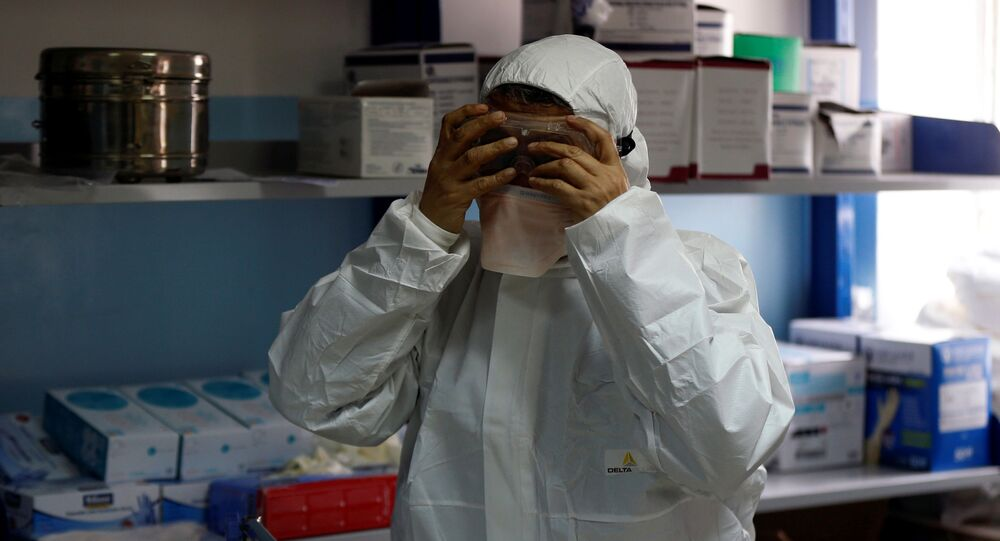 A member of the medical staff puts on protective gear at a new section specialised in receiving any person who may have been infected with coronavirus, at the Al-Bashir Governmental Hospital in Amman, Jordan January 28, 2020