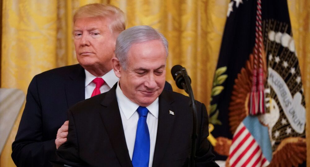 US President Donald Trump puts his hands on Israel's Prime Minister Benjamin Netanyahu's shoulders as they deliver joint remarks on a Middle East peace plan proposal in the East Room of the White House in Washington, 28 January 2020.