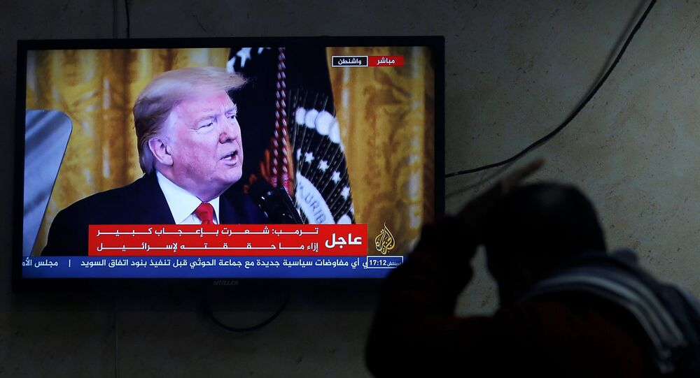 A Palestinian man watches a television screen broadcasting the announcement of Mideast peace plan by U.S. President Donald Trump