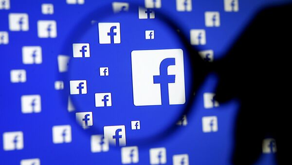 A man poses with a magnifier in front of a Facebook logo on display in this illustration taken in Sarajevo, Bosnia and Herzegovina, December 16, 2015 - Sputnik International