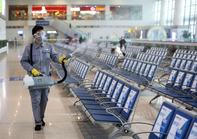 Workers in protective mask disinfects a waiting hall following the outbreak of a new coronavirus at the Nanjing Railway Station, in Nanjing