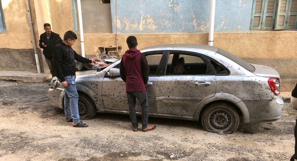 Libyan boys check a damaged car after a shell fell on a residential area at Hadba al-Badri district, in Tripoli