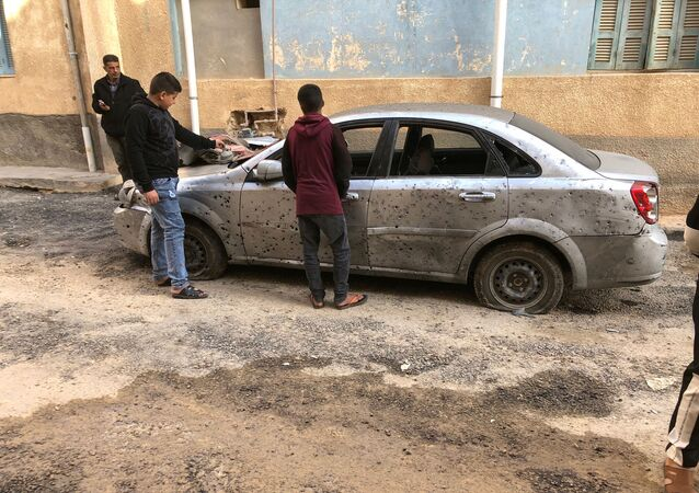 Libyan boys check a damaged car after a shell fell on a residential area at Hadba al-Badri district, in Tripoli