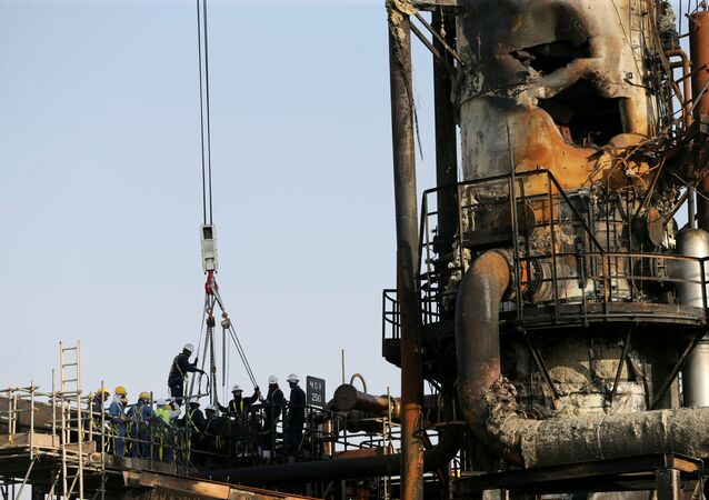 Workers are seen at the damaged site of Saudi Aramco oil facility in Abqaiq, Saudi Arabia