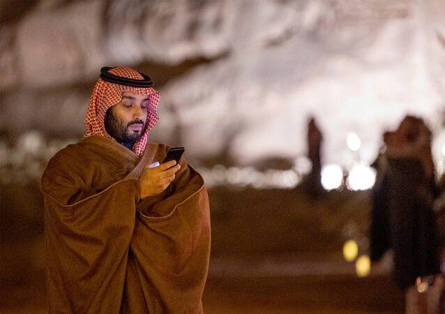 Saudi Arabia's Crown Prince Mohammed bin Salman uses his phone during a meeting with Japan's Prime Minister Shinzo Abe in Riyadh