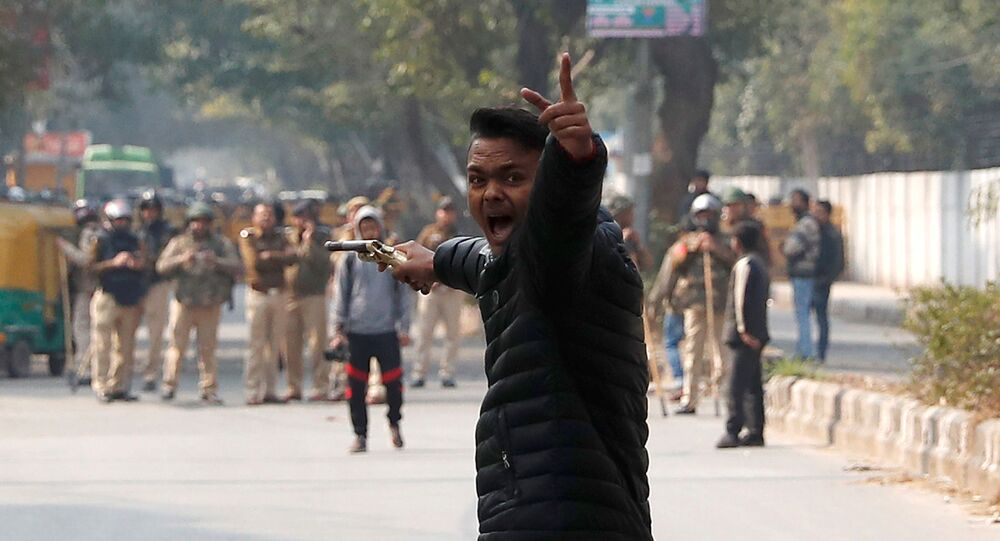 An unidentified man reacts as he brandishes a gun during a protest against a new citizenship law outside the Jamia Millia Islamia university in New Delhi, India, January 30, 2020