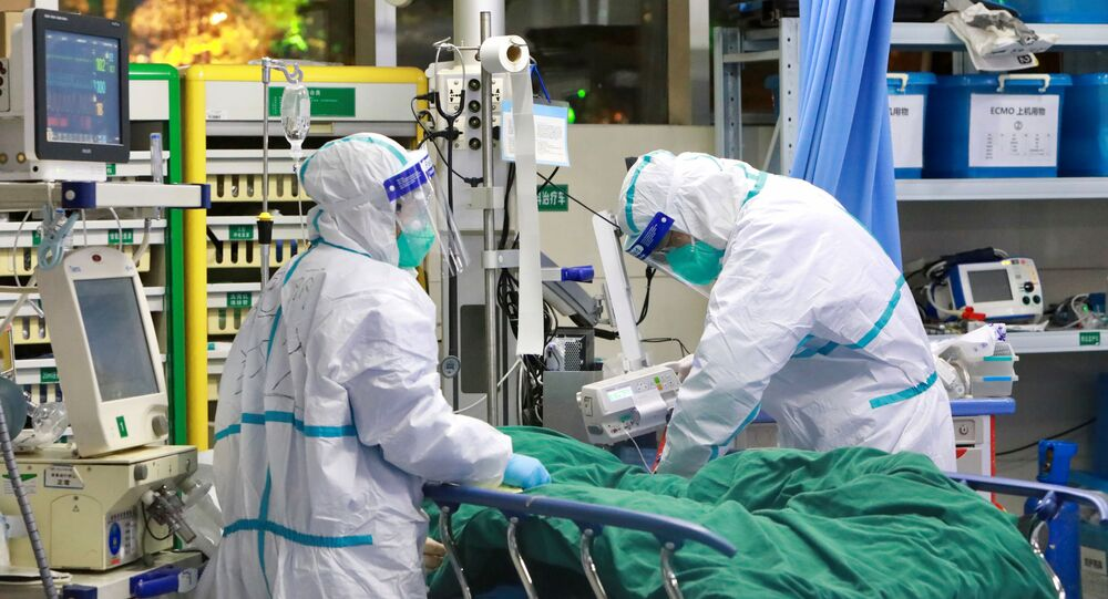 Medical staff in protective suits treat a patient with pneumonia caused by the new coronavirus at the Zhongnan Hospital of Wuhan