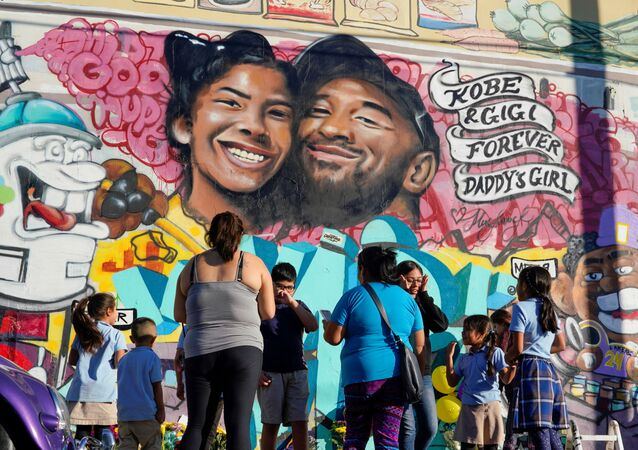 Fans gather around a mural in Los Angeles to pay their respects to Kobe Bryant after a helicopter crash took the life of the retired basketball star, 28 January 2020.