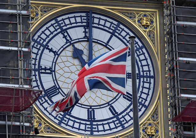 The British union flag is seen fluttering as the clock face of Big Ben shows eleven o'clock, London, January 30, 2020.