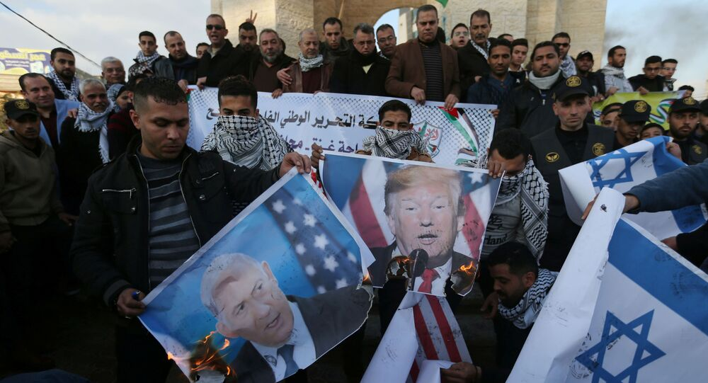 Palestinian demonstrators burn pictures depicting U.S. President Donald Trump and Israeli Prime Minister Benjamin Netanyahu, and repsentations of U.S and Israeli flags during a protest against the U.S. President Donald Trump's Middle East peace plan, in the southern Gaza Strip January 29, 2020
