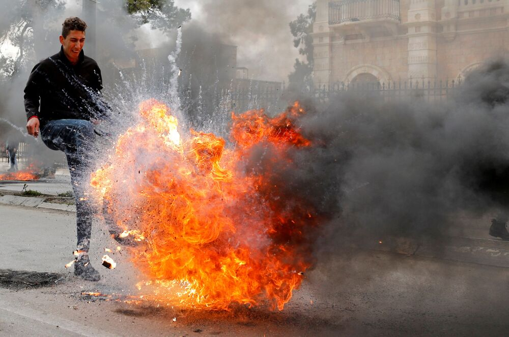 A Palestinian demonstrator kicks a burning tire during a protest against the U.S. president Donald Trump's Middle East peace plan, in Bethlehem in the Israeli-occupied West Bank January 29, 2020.