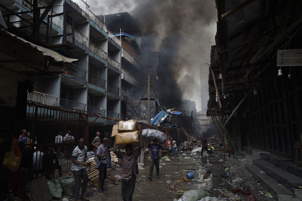 People carry goods salvaged from a fire that broke out in a section of the Balogun market in Lagos on January 29, 2020.