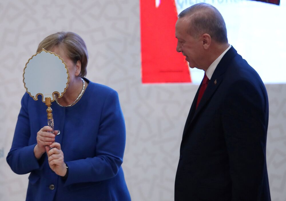 German Chancellor Angela Merkel receives a gift from Turkish President Tayyip Erdogan during the official opening ceremony of Turkish-German University's new campus in Istanbul, Turkey, January 24, 2020.