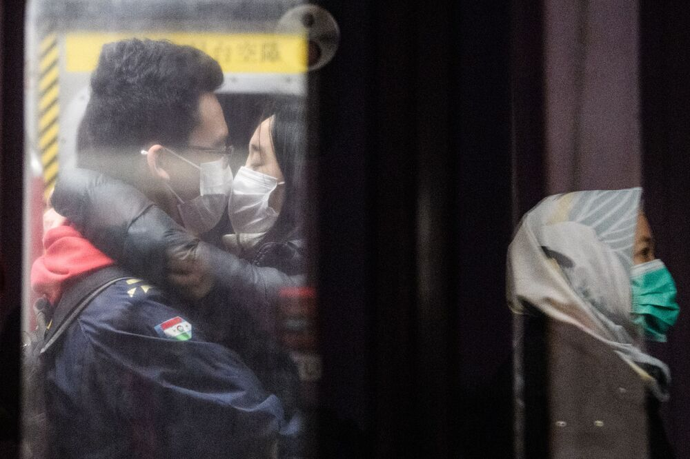 A couple wearing face masks kiss on an underground metro train as another passenger (R) is reflected on a platform glass door during a Lunar New Year of the Rat public holiday in Hong Kong on January 27, 2020, as a preventative measure following a coronavirus outbreak which began in the Chinese city of Wuhan.