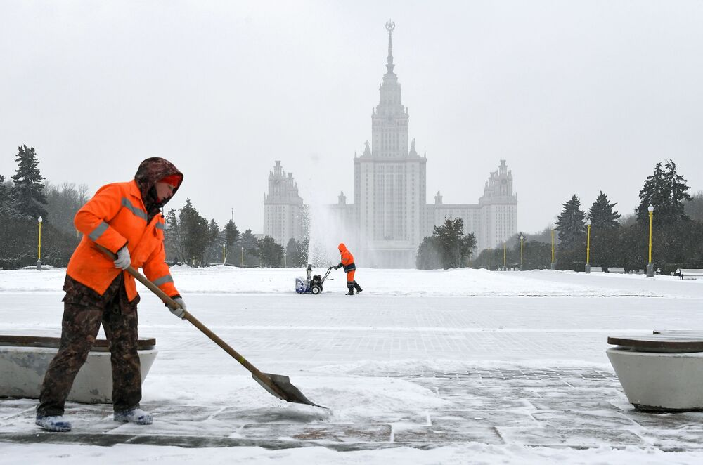 City service workers clean snow near the Moscow State University building