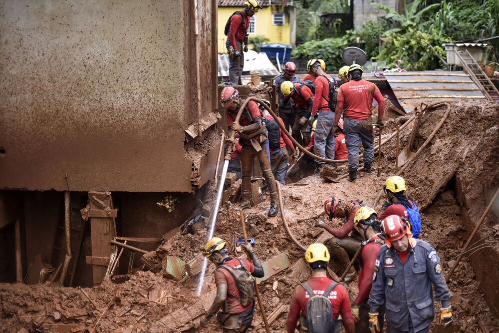 Firefighters search for missing persons using a hydraulic dismantling technique, which uses water to disperse mud, after a landslide in Vila Bernadete, Belo Horizonte, Minas Gerais state, Brazil, on January 26, 2020.